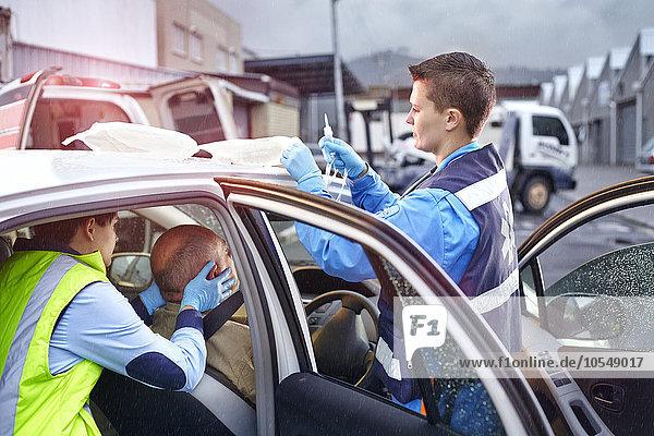 Rettungskräfte  die zum Opfer eines Autounfalls im Auto tendieren