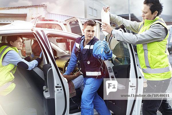 Rettungskräfte mit IV-Beutel  die zum Unfallopfer im Auto tendieren
