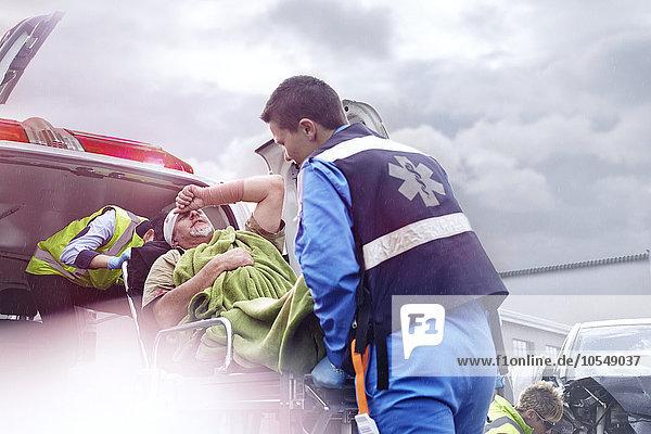 Rettungskräfte beim Verladen des Unfallopfers in den Krankenwagen