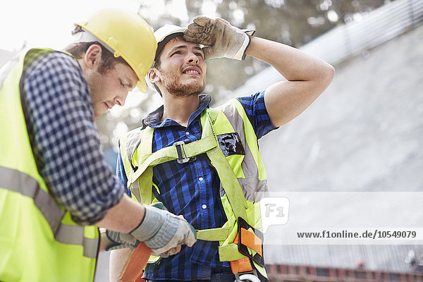 Bauarbeiter beim Befestigen von Mitarbeiter-Sicherheitsgurten