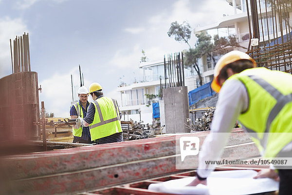 Engineer reviewing blueprints at construction site
