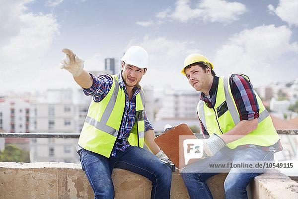 Bauarbeiter und Ingenieur mit Zwischenablage auf der Hochbaustelle
