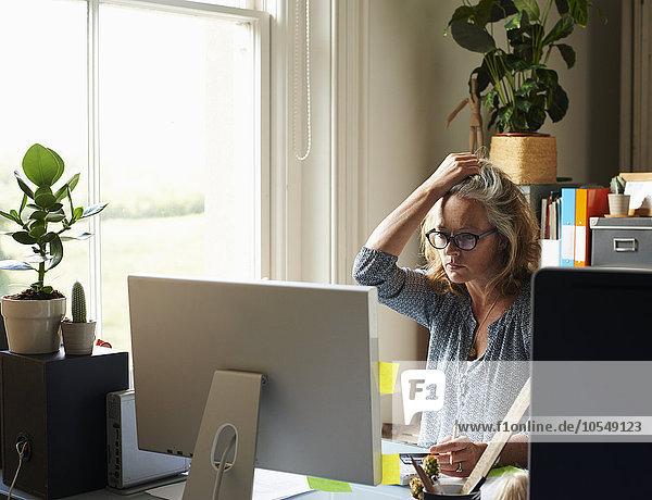 Gestresste Frau mit Hand im Haar hält Kreditkarte am Computer im Home-Office