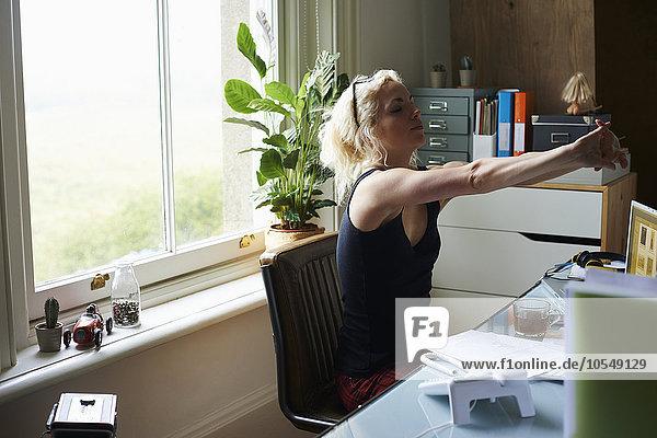 Junge Frau mit ausgestreckten Armen am Schreibtisch im Home-Office
