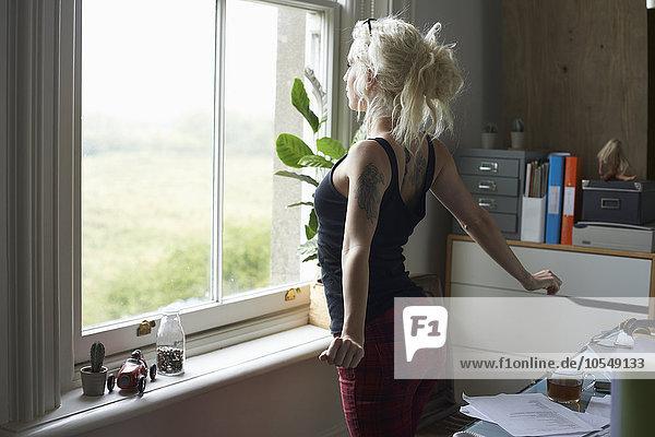 Junge Frau streckt sich am Fenster im Home-Office