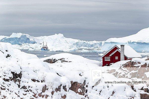 Rote grönländische Hütte  Haus auf einer Halbinsel  vor großen Eisbergen mit Fischerboot  Ilulisaat  Grönland  Nordamerika