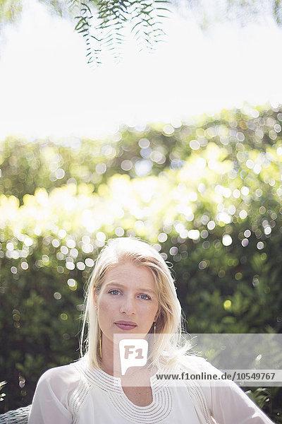 Porträt einer blonden Frau  die in einem Garten steht.