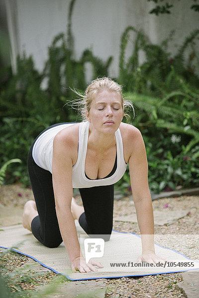 Blonde Frau beim Yoga in einem Garten.