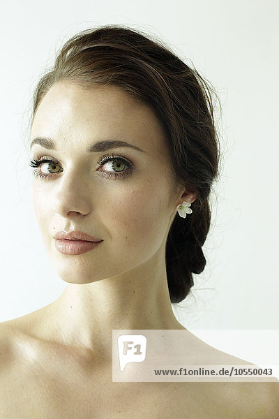 Portrait of a woman with brown hair tied in an elegant bun.