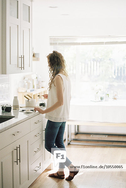 Woman standing in a kitchen preparing a pot of tea.