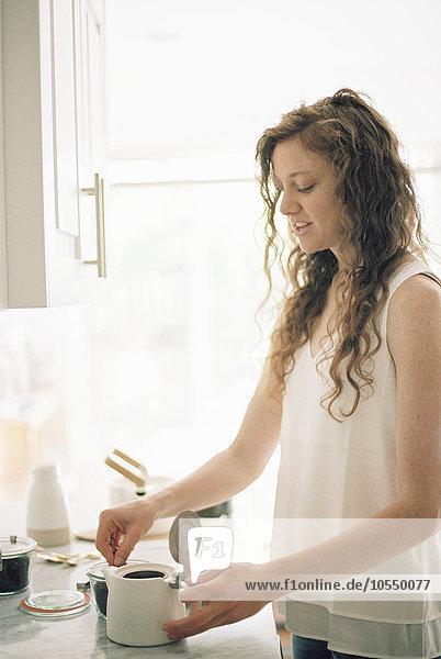 Frau  die in einer Küche steht und eine Kanne Tee zubereitet.
