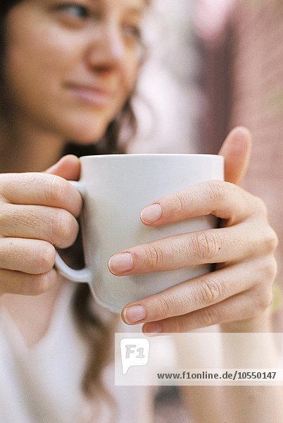 Nahaufnahme einer Frau  die eine Teetasse hält.