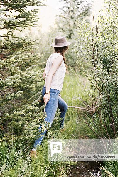 Frau in Jeans und mit Hut  die durch einen Wald geht.