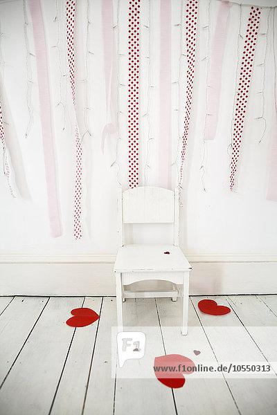 Leerer Stuhl in einem Fotografenstudio  Lichterketten und rote Luftschlangen an der Wand  herzförmige Papierschnipsel auf dem weißen Holzboden.