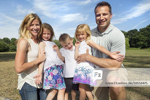 Familie mit drei Kindern in einem Park  die für ein Bild posieren.