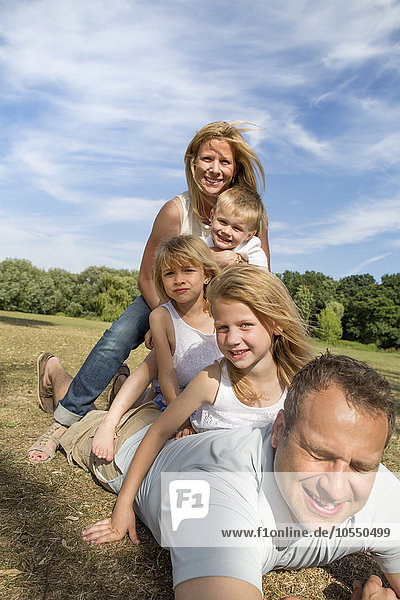 Family with three children playing in a park.