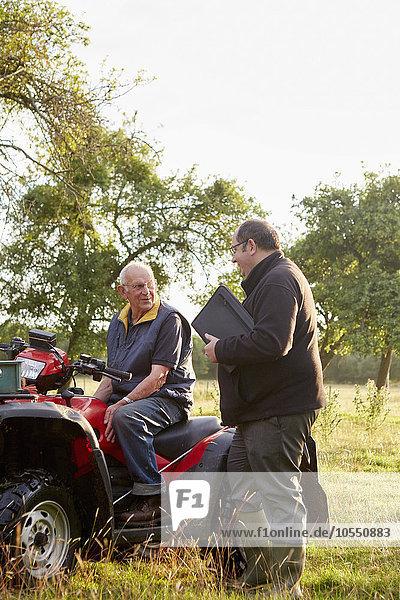 Zwei Männer  ein Landwirt und ein Mann mit einem Klemmbrett  mit einem Quad in einem Obstgarten.