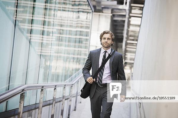 Ein Mann  der eine Computertasche mit einem Gurt auf einem Bürgersteig der Stadt trägt.