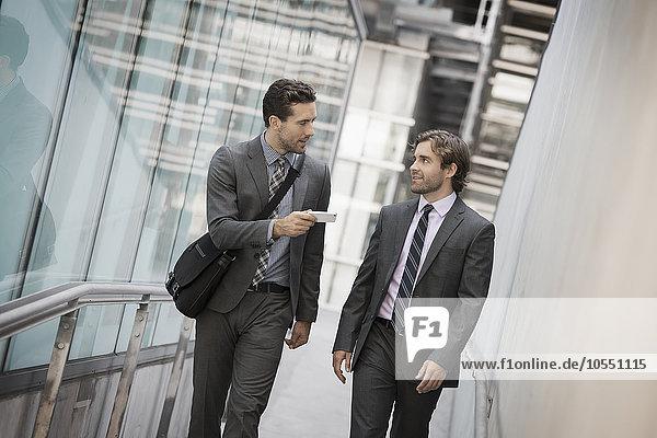 Zwei Männer in Geschäftsanzügen vor einem großen Gebäude  einer mit einem Smartphone in der Hand.