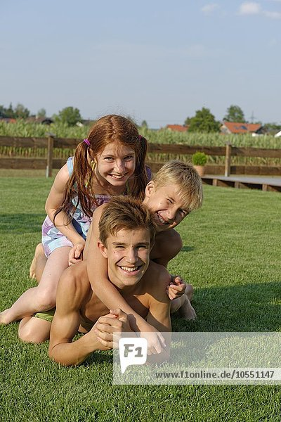 Girls and boys  kids  teens  siblings in the garden  having fun  Upper Bavaria  Bavaria  Germany  Europe