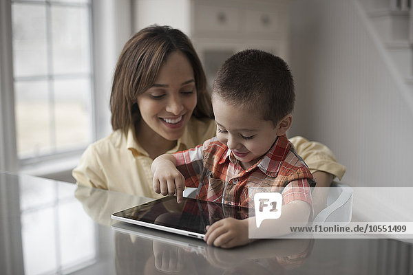 A mother and child looking at the screen of a digital tablet  the boy touching the screen.