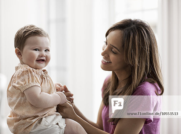 Eine Mutter und ihre Tochter  eine Frau  die die Hände eines kleinen Kindes hält und lächelt.