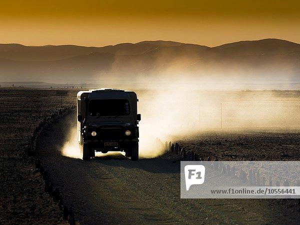 Landrover fährt im Kulala Wilderness Reserve  Namib-Wüste am Abend  Gegenlicht  Hardap  Namibia  Afrika