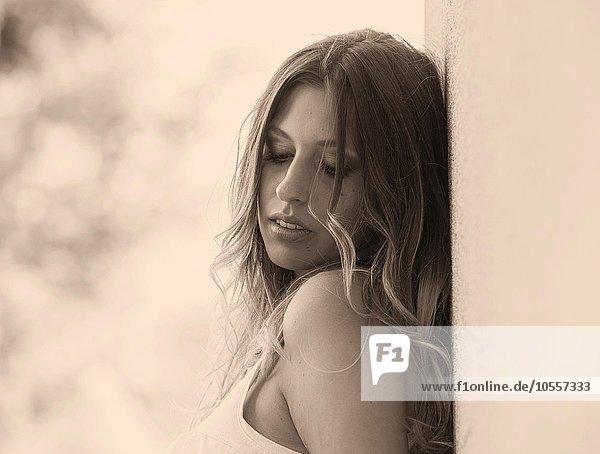 Junge  hübsche Frau mit langen Haaren  Portrait  lehnt an Wand