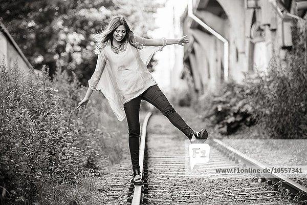 Junge Frau balanciert lachend auf Schienen Junge Frau balanciert lachend auf Schienen