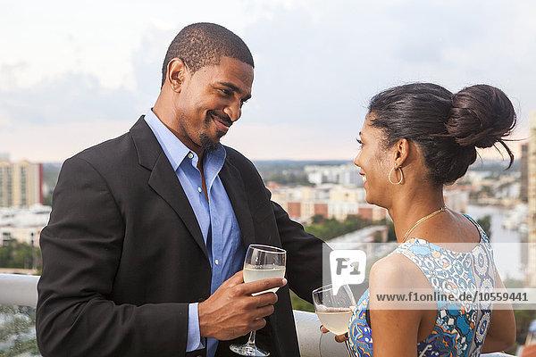 Couple drinking wine on urban balcony
