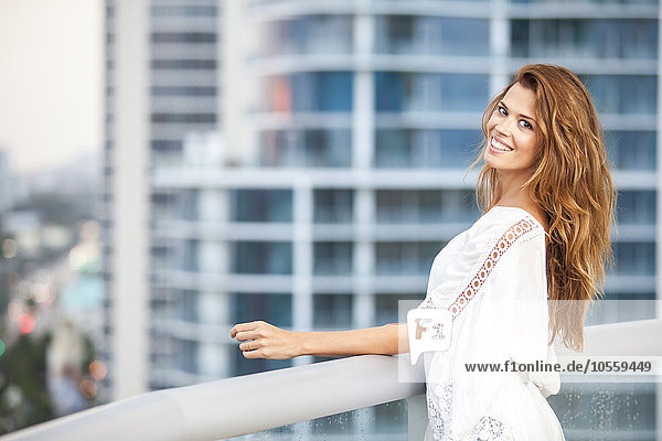Hispanic woman standing on urban balcony