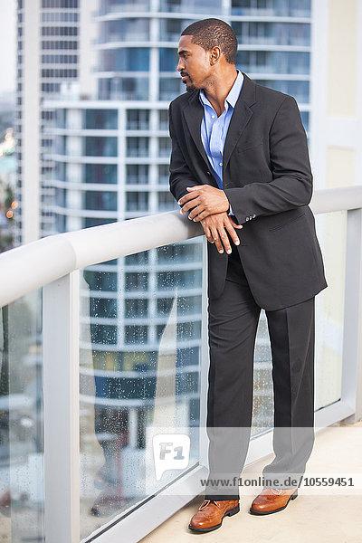 African American businessman standing on urban balcony