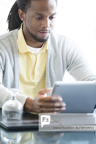 African American businessman using digital tablet in restaurant