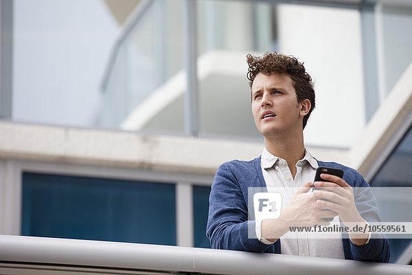 Caucasian businessman using cell phone on balcony