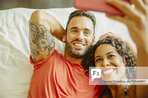 Couple taking selfie with cell phone on bed