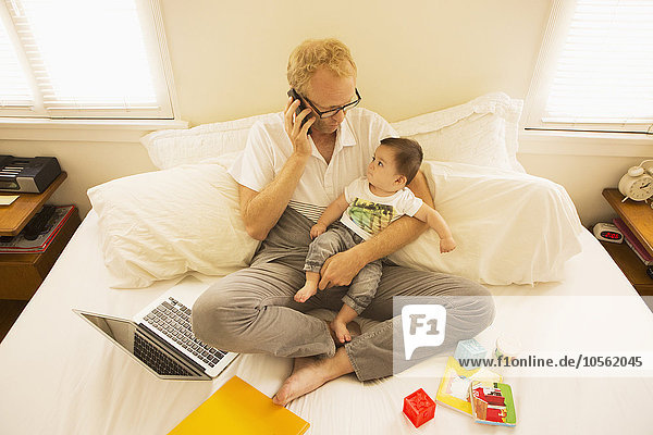 Father holding son and talking on cell phone on bed