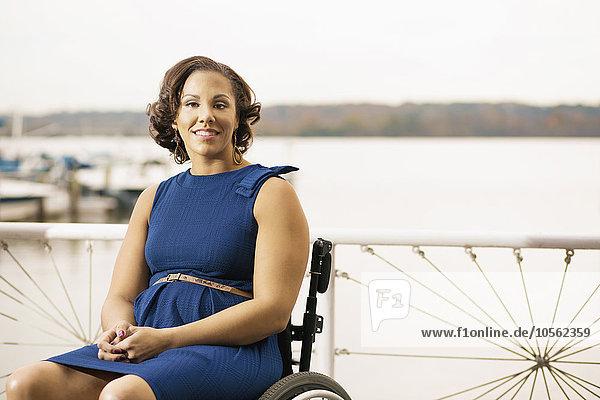 Frau lächeln Behinderung Rollstuhl