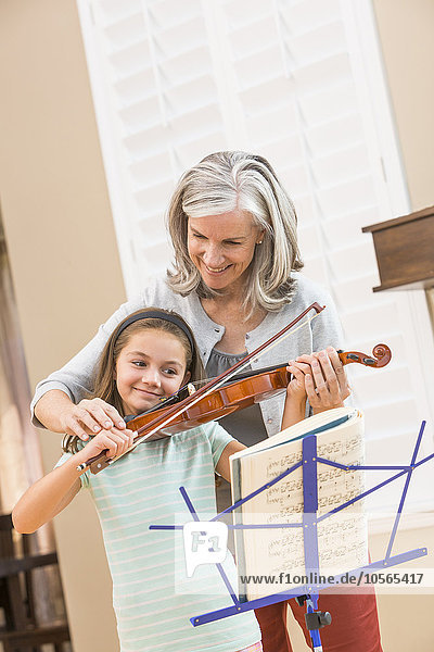 Caucasian woman giving student violin lessons