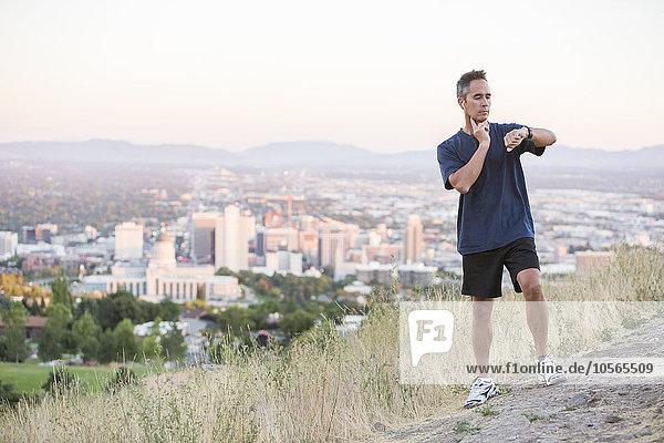 Mixed race man checking pulse on hilltop over Salt Lake City  Utah  United States
