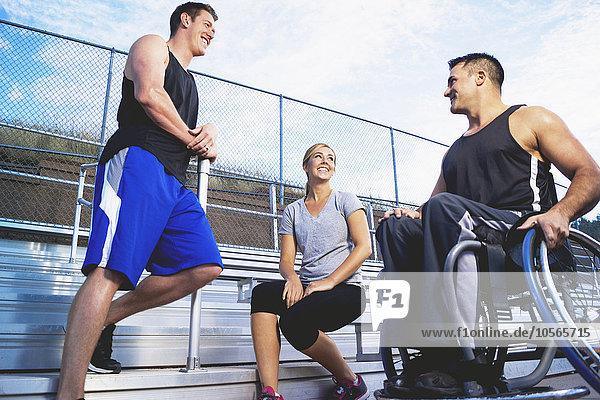 Behindertensport Freundschaft Athlet unüberdachte Tribüne Rollstuhl