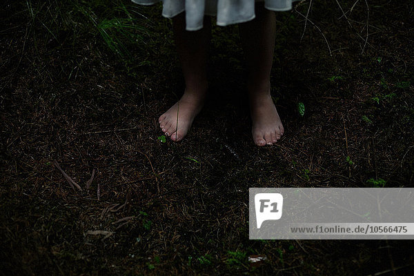 Caucasian girl with bare feet in dirt