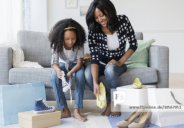 Mother and daughter trying on shoes on sofa