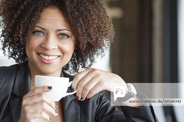 Mixed race woman drinking coffee in cafe