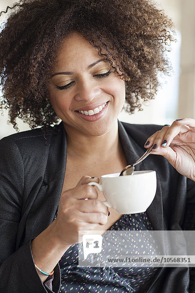 Mixed race businesswoman drinking cup of coffee