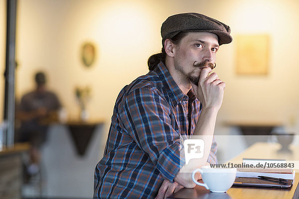 Caucasian man thinking in cafe