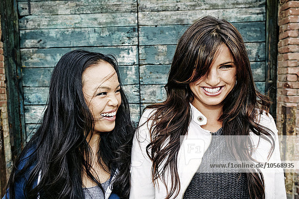 Women laughing at wooden wall