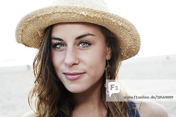 Mixed race woman wearing straw hat