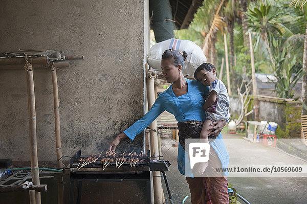 Außenaufnahme kochen Sohn Grill Mutter - Mensch freie Natur
