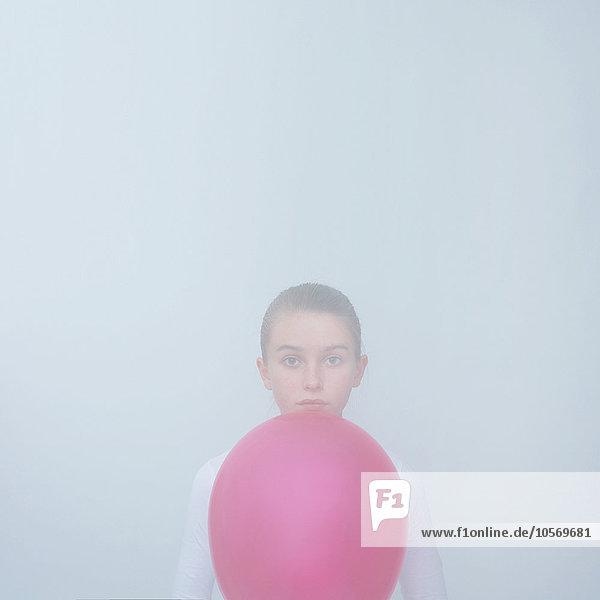 Caucasian teenage girl holding balloon