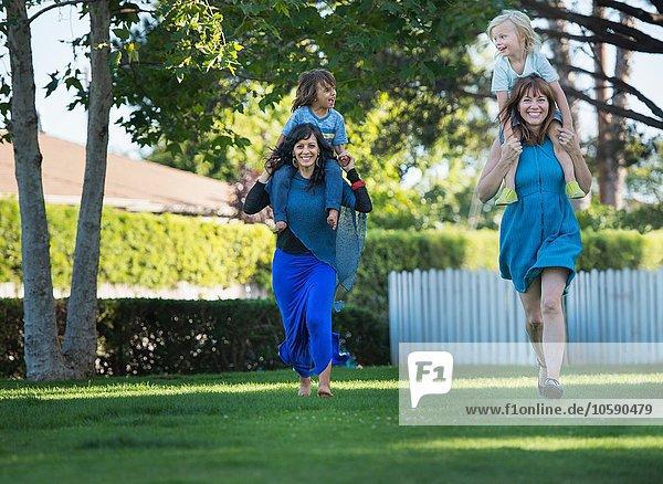 Zwei Mütter mit Kindern auf den Schultern  Rennen  im Freien